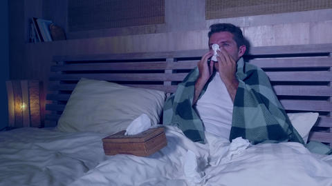 man lying in bed suffering grippe feeling unwell and sick sneezing and blowing Live Action