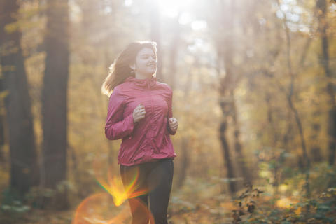 Young woman running during autumn forest フォト