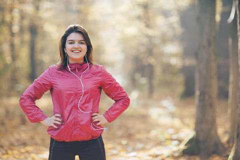 Portrait of a girl who trains and listens to music in the morning autumn park Fotografía