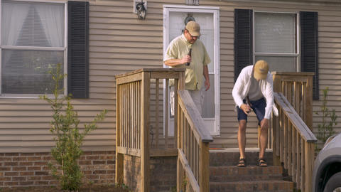 Two male friends sit on porch steps together talking and holding beer bottles on Footage