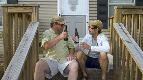 Authentic moment between two male friends cheering with beer bottles while Footage