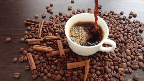 Pouring coffee in white cup surrounded by coffee beans on dark background Archivo