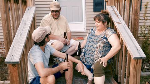 Three friends including two men and a woman sitting on porch steps cheering with Footage