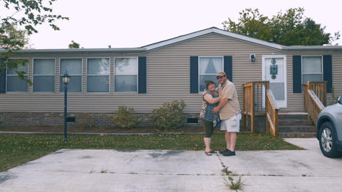 Portrait of a happy heavy couple hugging in front of a manufactured home and Footage