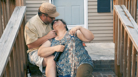 Happy plus sized couple in their 30s or 40s kissing and embracing while sitting Footage