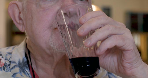 Close up of an elderly senior man drinking red wine and chewing food in a Footage