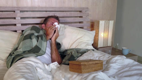 Man in bed coughing sneezing and blowing nose sick with grippe feeling unwell Live Action