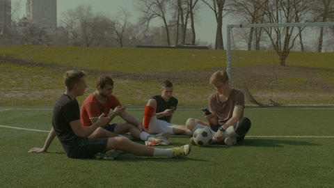 Football team with smart phones resting on soccer field 画像