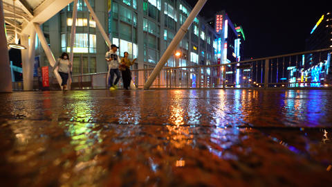 People walk through Osaka at night in the rain Footage