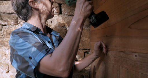 Masculine woman in her 40s preparing to drill a hole with a cordless drill power Footage