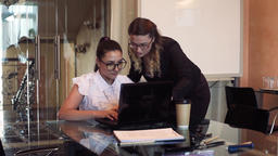 Two business women working in the office using a computer Footage