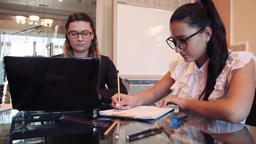 Two business women working on a business project in an office sitting at a table Footage