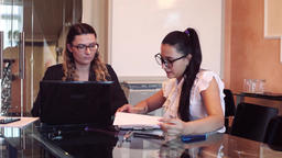 Two business women wearing glasses in business clothes discussing a business Footage