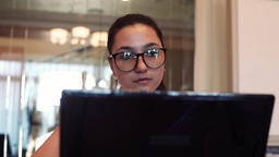 Business woman in glasses works using computer and mobile phone sitting at table Footage