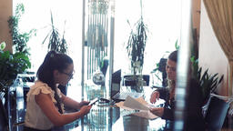Two business women discussing a business project while sitting at a table in an Footage