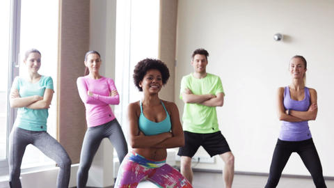 group of smiling people dancing in gym or studio Footage