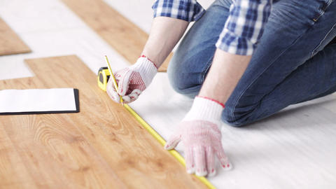 close up of man measuring flooring and writing Footage