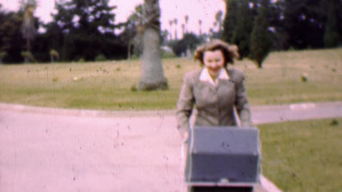 1957: Mother prepares baby stroller in tropical cemetery park Footage