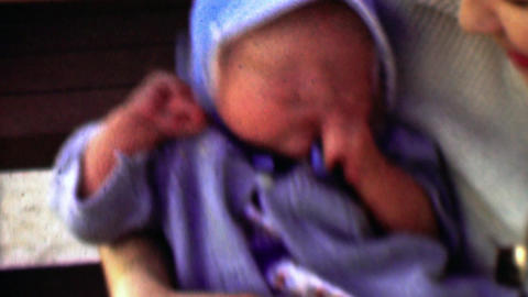 1957: Newborn baby boy in blue bonnet hat trying to get comfortable Footage