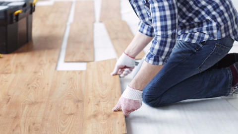 close up of man installing wood flooring Live Action