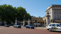 Camera tracks London taxi across the front of Buckingham Palace. Shot on a sunny Footage