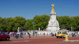 Static shot of traffic passing the Victoria Memorial outside Buckingham Palace.  Footage