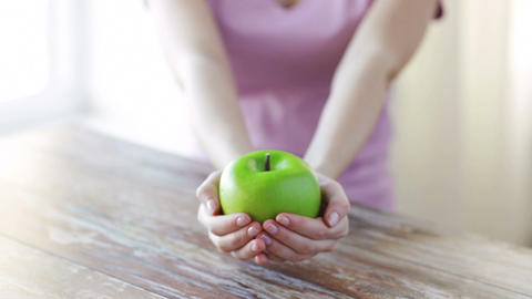 close up of young woman hands showing green apple Footage