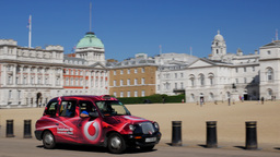 Camera tracks London taxi in front of Horse Guards Parade and Whitehall. Shot on Footage