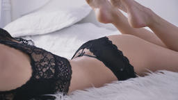Close-up of a young sexy Caucasian female body in black underwear lying on a bed Footage