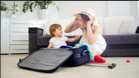 Young mother having fun with her toddler son while packing suitcase フォト