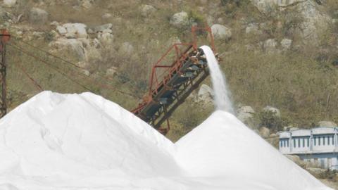 Closeup Conveyor Belt Pours Salt Stream to Heap Footage