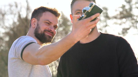 Young gay couple taking photo of themself on a film camera in the spring evening Footage