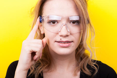 Woman with futuristic smart glasses on her eyes フォト