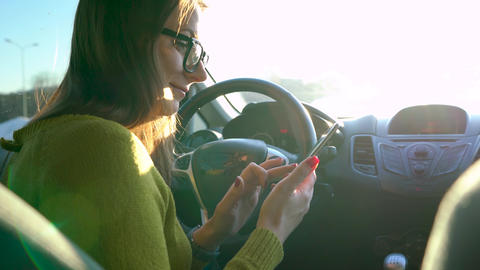 Woman in glasses using a smartphone in the car, fastens the seat belt and drives Footage