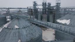 Flight under granaries and elevators or oil storage on winter background 영상물