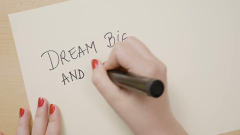 Female hands writing dream big and dare to fail exclamation point motivational Footage