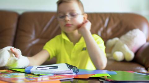 Little boy with broken hand don't want to make his school homework Footage