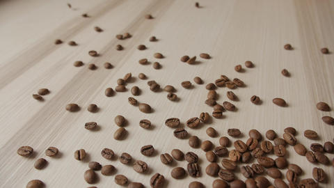 Roasted coffee beans spilling out on wooden plank Live Action
