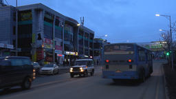 Evening view of building of shopping center, automobiles driving on city road Footage