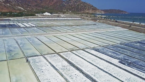 People Collect Salt on Fields Surrounded by Hills 영상물