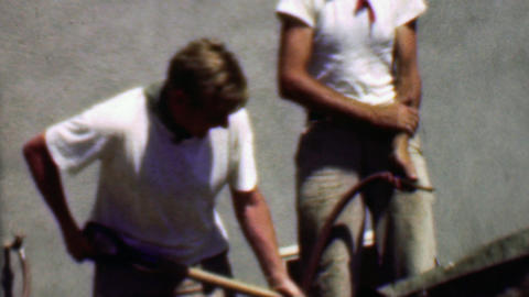 1957: Construction workers mix concrete in wheelbarrow with toddler Footage