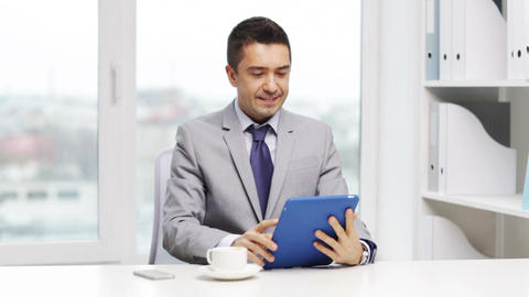 smiling businessman with tablet pc drinking coffee Footage