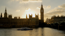 Thames river boat passes under Westminster Bridge as the sun sets behind parliam Footage