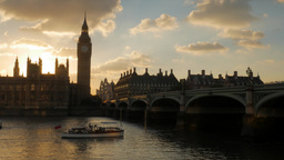 River boat passes under Westminster Bridge at the moment the sun sets behind the Footage
