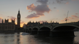 Small luxury boat passes under Westminster Bridge as the sun sets behind parliam Footage