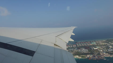 Wing Of Airplane Flying Above Ocean And City stock footage