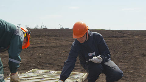 Man Looks at Prospecting Pit Makes Notes in List 영상물