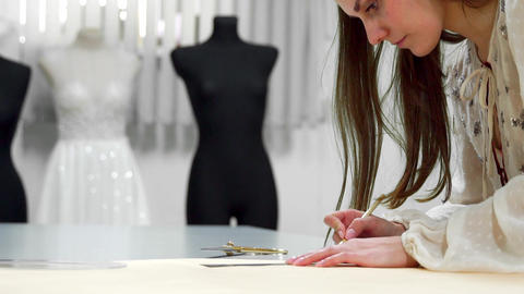 Beautiful girl fashion designer draws on the paper templates for cutting out Footage