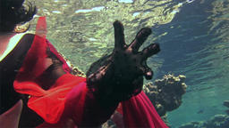 Young girl model free diver underwater in red costume of pirate in Red Sea Footage