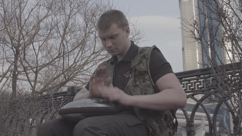 Russian man playing hapi drum side view Archivo